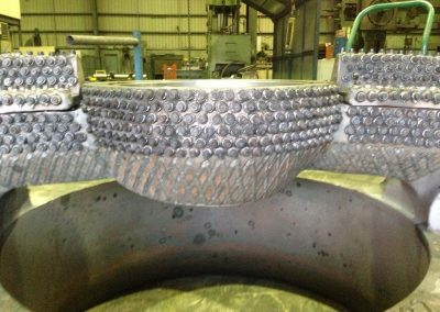 Cone crusher wear studs and hardfacing